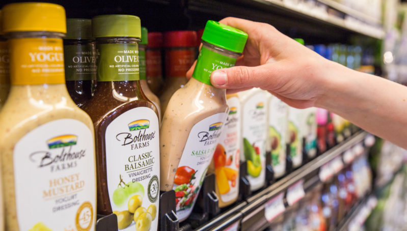 Customer reaching for a bottle of salad dressing on an organized SpaceDriver II pusher tray display